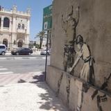 パレスチナの女の子がイスラエル軍人のボディチェックをする分離壁の有名な落書き