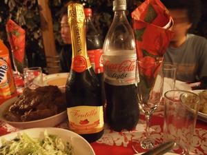 シャンパンとコーラを持ってクリスマスパーティーに参加