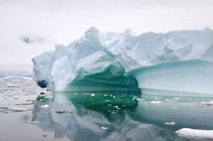 南極の海に浮かぶ巨大な流氷の近くをボートで通る