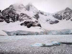 岩肌むき出しの山々と青く光る氷河が美しい南極のルーメア海峡