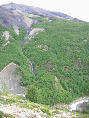 山に滝、川。歩いている道と崖を挟んで見えるパイネの景色