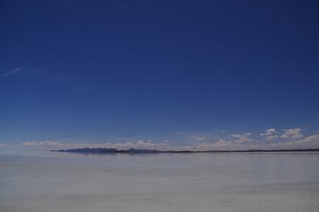四駆のルーフの上から眺めるどこまでも続くウユニ塩湖の真っ白な世界はかなり幻想的