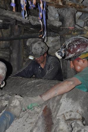 ポトシの鉱山で働く男達。トロッコの石をぶちまける